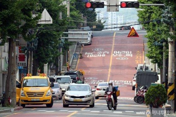 22일 인천의 한 어린이 보호구역에서 오토바이와 차량이 중앙선을 넘어 주행하는 모습./사진=이기범 기자 leekb@