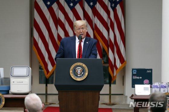 """[워싱턴=AP/뉴시스]도널드 트럼프(오른쪽) 대통령이 11일(현지시간) 백악관 로즈가든에서 신종 코로나바이러스 감염증(코로나19) 브리핑을 하고 있다. 트럼프 대통령은 중국에 유리한 조건으로 무역 합의 재협상이 이뤄질 가능성에 관한 기자 질문에 """"전혀 관심 없다""""라고 밝히며 """"중국이 서명한 합의를 잘 지키는지 보자""""라고 말했다. 2020.05.12."""