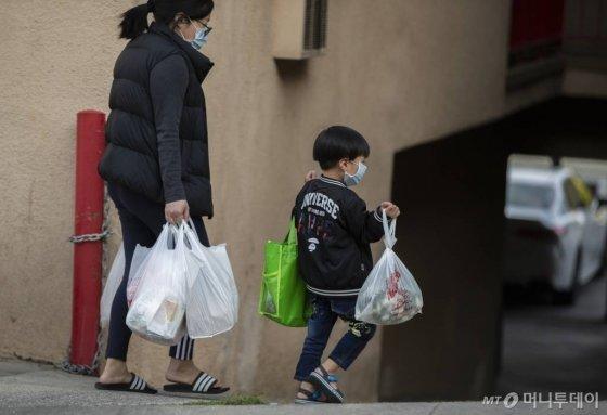 [로스앤젤레스=AP/뉴시스] 2일 미국 로스앤젤레스의 차이나타운에서 마스크를 착용한 여성과 어린이가 양손 가득 짐을 들고 이동 중이다. 미국에서도 신종 코로나바이러스 감염증(코로나19)과 연관된 것으로 의심되는 어린이 괴질 중환자가 나왔다고 CNN은 28일(현지시간) 보도했다. 스페인과 영국, 이탈리아 등에서는 이미 관련 질병으로 인한 어린이 사망 사례가 보고됐다. 2020.4.29.