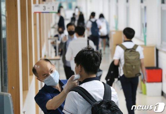고등학교 3학년 학생들의 등교가 시작된 지난 20일 오전 대전 전민동 전민고등학교에서 학생들이 발열검사를 받고 입실하고 있다. 신종 코로나바이러스 감염증(코로나19) 여파로 80일 만에 학생들의 등교 개학이 이뤄졌다. 2020.5.20/뉴스1 © News1 김기태 기자