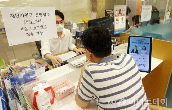 정부 긴급재난지원금 현장 신청 첫 날인 18일 오전 서울 중구 우리은행 을지로지점에서 시민들이 상담을 받고 있다. / 사진=김휘선 기자 hwijpg@