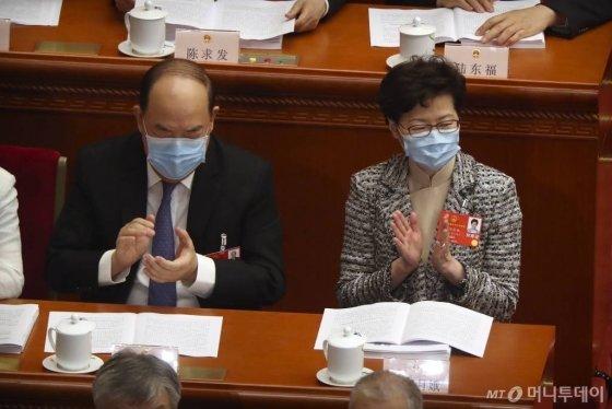 [베이징=AP/뉴시스]5월22일(현지시간) 중국 베이징 인민대회당에서 중국 최대 정치 행사인 전국인민대표회의(전인대)가 열리고 있는 가운데 캐리 람 홍콩 행정장관(오른쪽)이 신종 코로나바이러스 감염증(코로나19)을 막기 위해 마스크를 쓴 채 박수를 치고 있다.  2020.05.22.