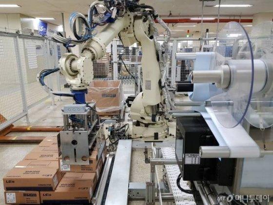 청주시 흥덕구 일반산업단지에 위치한 LS ELECTRIC 제1사업장에서 로봇 팔이 파레트에 수출용 제품을 적재하고 있는 모습/사진=이정혁 기자
