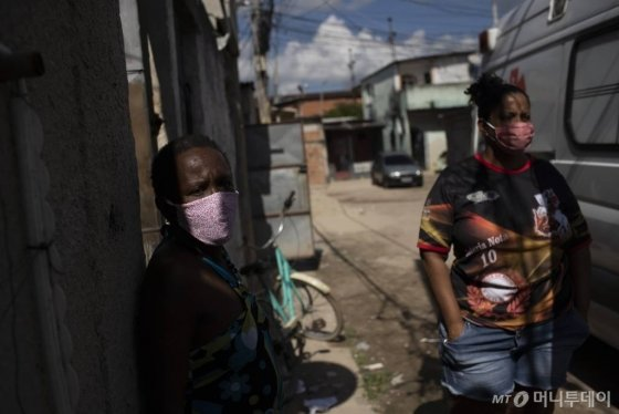 [리우데자네이루=AP/뉴시스]19일(현지시간) 브라질 리우데자네이루의 빈민가에서 의료진이 신종 코로나바이러스 감염증(코로나19) 증세로 의심되는 한 남성을 살피는 동안 가족들이 밖에서 대기하고 있다. 브라질의 코로나19 사망자가 하루 새 1179명 추가됐는데 하루 1000명 이상 숨진 사례는 이번이 처음이다. 이로써 누적 사망자는 1만7971명이 됐으며 확진자 수는 27만1628명으로 확진자 수로는 세계 3번째 규모가 됐다. 2020.05.20.