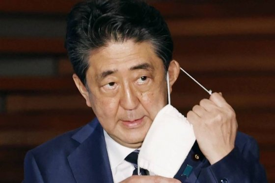 [도쿄=AP/뉴시스]아베 신조 일본 총리가 21일 기자회견에서 마스크를 벗고 있다. 일본 정부는 이날 3개 지역에 대해 긴급사태 선언 추가 해제를 발표했다. 도쿄 등 5개 지역에 대해서는 오는 25일 다시 검토하겠다고 밝혔다. 2020.05.22.