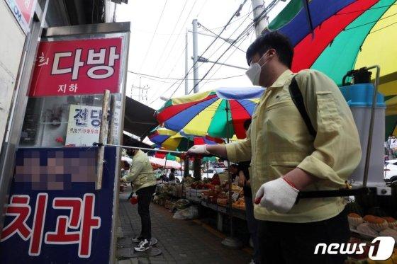 이태원 클럽발' 신종 코로나 바이러스 감염증(코로나19) 지역 확산이 이어지고 있는 26일 오후 확진자가 방문한 서울 성동구 식당 인근 금남시장에서 금호동주민센터 관계자가 방역작업을 하고 있다./사진=뉴스1