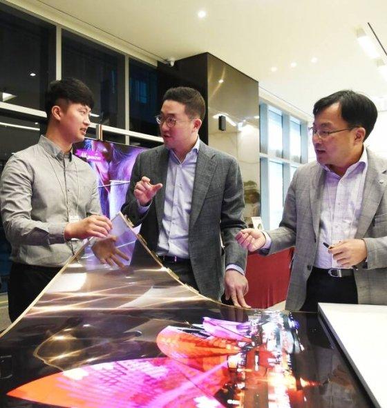 2018년 9월 LG사이언스파크를 찾은 구광모 회장이 윤수영 LG디스플레이 연구소장(오른쪽)과 담당 연구원과 함께 투명 플렉시블 OLED를 살펴보고 있다/사진제공=LG