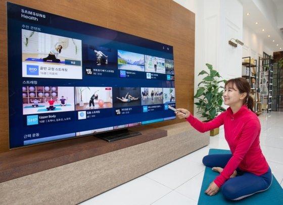 삼성전자 모델이 2020년형 삼성 스마트 TV용 '삼성 헬스' 앱으로 홈 트레이닝 영상을 시청하고 있다. /사진제공=삼성전자