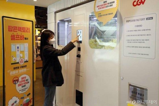 CJ CGV가 대면 서비스를 최소화한 '언택트시네마'를 선보인 가운데 지난달 21일 서울 CGV 여의도에서 한 시민이 직원과 대면 없는 셀프 벤딩머신을 이용해 팝콘을 구매하고 있다. '언택트시네마'는 다양한 하이테크 기술을 통해 언택트(Un-tact) 서비스를 기반으로 새롭고 간편하게 극장 시설을 이용할 수 있는 서비스다. / 사진=이기범 기자 leekb@