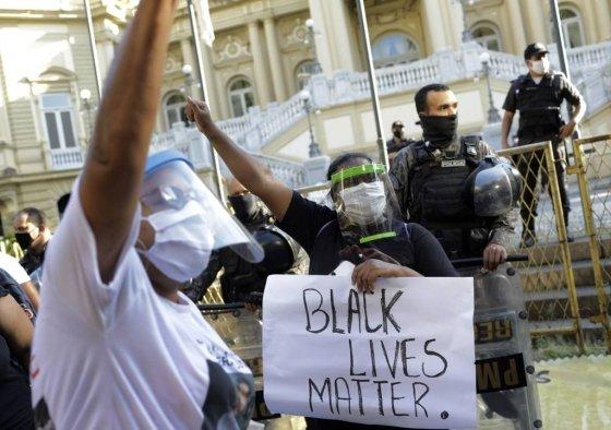 """[리우데자네이루=AP/뉴시스]5월 31일(현지시간) 브라질 리우데자네이루 주 정부 청사 앞에서 최근 경찰의 빈민 지역 흑인들에 대한 폭력에 항의하는 시위가 열려 마스크를 쓴 사람들이 """"흑인 생명도 소중하다""""라는 손팻말을 들고 시위하고 있다. 이들 중 일부는  미국에서 경찰의 과잉 진압으로 숨진 흑인 남성 조지 플로이드가 호소했던 """"숨을 쉴 수가 없다""""(I can't breathe)라는 말을 외치며 시위를 벌였다. 2020.06.01."""