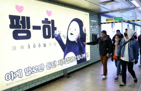 서울 강남구 삼성역에 설치된 펭수 데뷔 300일 기념 지하철 광고를 관광객들이 지나가며 바라보고 있다./ 사진=뉴시스