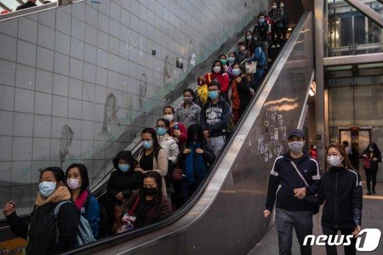 (홍콩 AFP=뉴스1) 지난 2월 9일(현지시간) 신종 코로나바이러스 감염증의 확산 속 홍콩의 한 에스컬레이터에 마스크를 쓴 시민들이 타고 있다.   ⓒ AFP=뉴스1