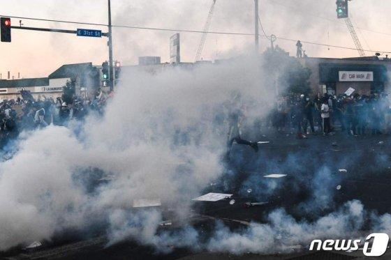 30일(현지시간) 미네소타주 미니애폴리스에서 흑인 남성 조지 플로이드의 사망에 항의하는 시위대와 경찰이 최루가스 속 격렬한 충돌을 하고 있다.  /사진=AFP·뉴스1