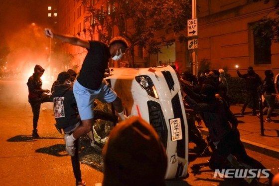 [워싱턴=AP 뉴시스] 5월 31일(현지시간) 미 워싱턴DC 백악관 근처에서 플로이드의 죽음에 항의하는 시위대가 한 자동차를 뒤집어 훼손하고 있다. 지난달 25일 미니애폴리스 경찰관의 과잉 진압으로 숨진 흑인 남성 조지 플로이드의 죽음을 두고 미국 곳곳에서 시위가 벌어지고 있다.