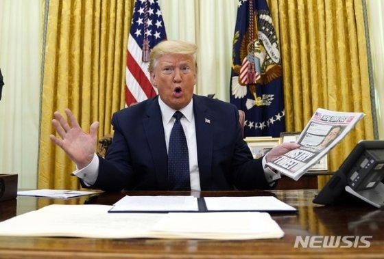 [워싱턴=AP/뉴시스]도널드 트럼프 미국 대통령이 28일(현지시간) 백악관 집무실에서 트위터 등 소셜미디어와 온라인 플랫폼 규제 행정명령에 서명하기 전 트위터에 관해 보도한 뉴욕포스트를 들어 보이고 있다. 2020.05.29.