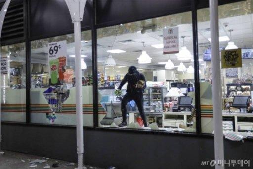[뉴욕=AP/뉴시스] 1일(현지시간) 한 시위자가 얼굴을 가린 채 뉴욕의 한 편의점에서 물건을 약탈하고 있다. 흑인 남성 조지 플로이드가 백인 경찰의 가혹 행위로 숨진 사건에 항의하는 시위가 약탈과 방화로 이어지며 폭력 시위의 우려도 높아지고 있다. 2020.6.2.