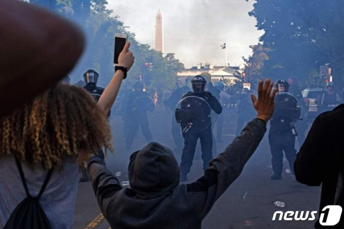 (AFP=뉴스1) 이동원 기자 = 도널드 트럼프 미국 대통령은 1일(현지시간) 흑인 남성 조지 플로이드의 사망에 항의하는 시위와 관련해 폭동 진압을 위해 군대를 동원할 수 있다고 말했다.  1일(현지시간) 워싱턴 D.C.에서 폭동 진압 장비를 착용한 경찰들이 흑인 조지 플로이드의 죽음에 대한 항의시위대를 향해 최루탄을 발사하며 백악관 밖에서 밀어내고 있다. 미국의 주요 도시들은 폭동을 진압하기 위해 통행금지를 당했다.  ⓒ AFP=뉴스1