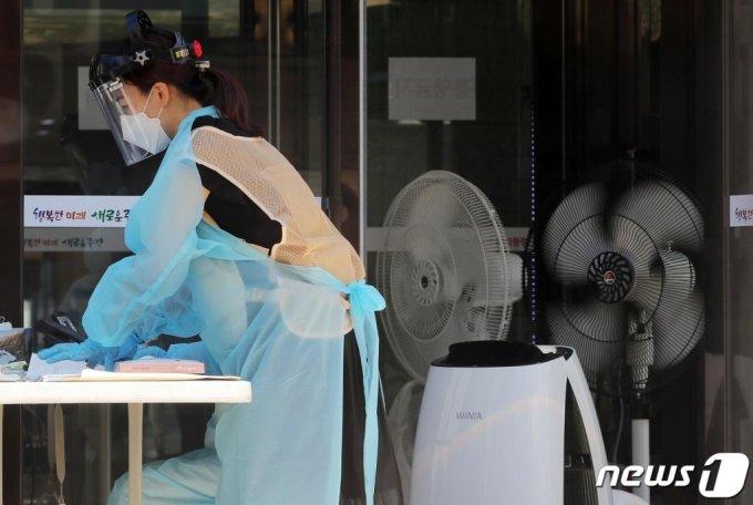 (서울=뉴스1) 구윤성 기자 = 무더위가 이어지고 있는 15일 오후 서울 중랑구 보건소에 마련된 신종 코로나바이러스 감염증(코로나19) 선별진료소에서 의료진이 선풍기와 아이스조끼 등으로 더위를 식히며 업무를 보고 있다. 2020.6.15/뉴스1