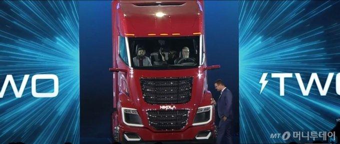 트레버 밀턴 니콜라자동차 CEO(자동차 밖 오른쪽)가 '니콜라월드 2019'에서 수소전기트럭인 니콜라TWO의 컨셉카를 선보이고 있다. /사진제공=니콜라모터 홈페이지 동영상 캡쳐.