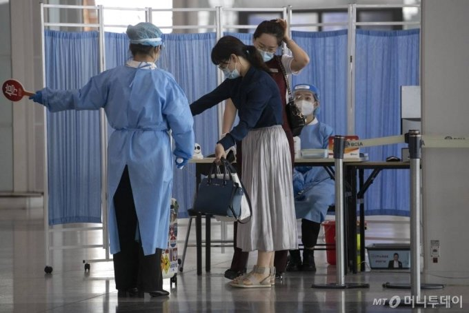 [베이징=AP/뉴시스]17일 중국 베이징의 베이징 수도공항 제2터미널에서 출입객들이 신종 코로나바이러스 감염증(코로나19) 관련 측정을 받고 있다. 수도 베이징의 코로나19 확진자 수가 증가하면서 당국은 상업항공편 60% 이상을 취소하고 코로나19 경계수위를 높였다고 관영매체가 보도했다. 2020.06.17.