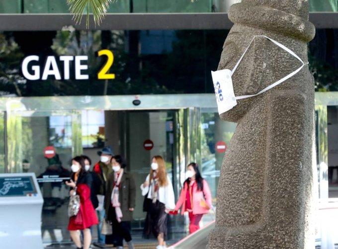 제주국제공항을 통해 관광객들이 입도하는 가운데 돌하르방이 코로나19 예방 마스크를 쓰고 있다. /사진=뉴시스