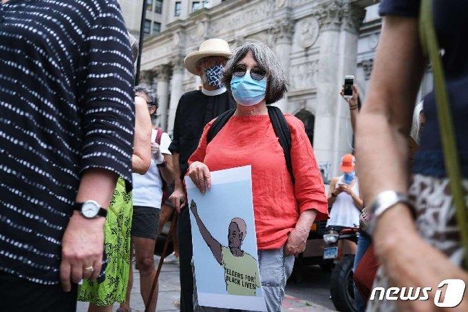 고령의 뉴요커가 24일(현지시간) 뉴욕시청 인근에서 열린 인종차별 반대 시위에 참여했다. © AFP=뉴스1