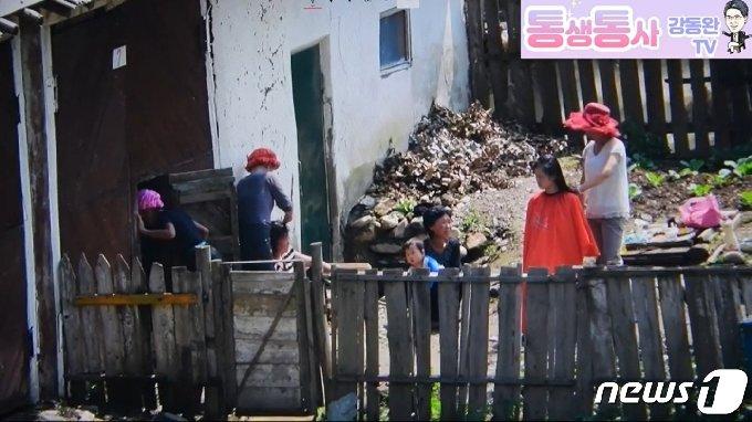 북한의 양강도 삼수군 지역 주민들이 마을 창고 뒤편에서 출장 미용 서비스를 받고 있다. ('통생통사 강동완 TV' 갈무리) © 뉴스1
