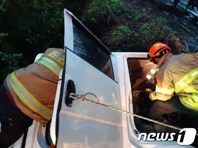 [사진] 소방당국, 빗길 속 사고난 트럭서 구조작업