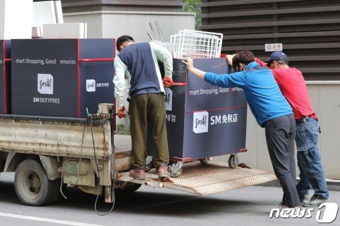 지난 4월 코로나19 영향으로 영업을 종료하는 서울 종로구 SM면세점 앞에서 관계자들이 짐을 옮기고 있다. /사진=뉴스1