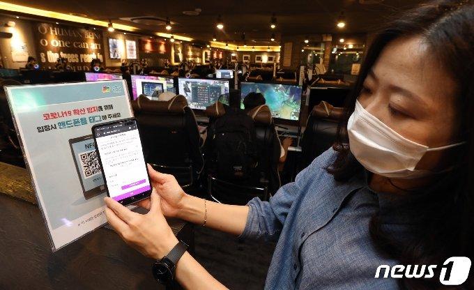 지난달 1일 서울 성동구의 한 PC방에서 이용객이 QR코드를 활용한 전자출입명부를 작성하고 있다. 2020.6.1/뉴스1 © News1 황기선 기자