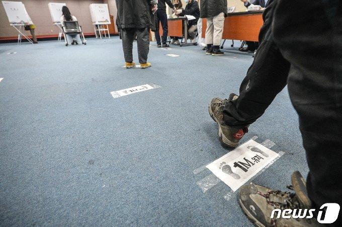 제21대 국회의원 선거일인 15일 오전 서울 성북구 북한산국립공원 탐방안내소에 마련된 정릉4동 제4투표소 바닥에 사회적 거리두기를 위한 안내문이 붙어 있다. 2020.4.15/뉴스1 © News1 성동훈 기자