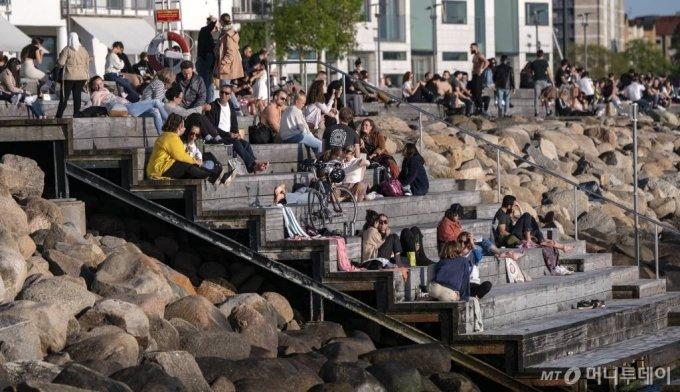 [말뫼(스웨덴)=AP/뉴시스]26일(현지시간) 스웨덴 말뫼에서 시민들이 따뜻한 저녁 날씨를 즐기며 나와 있다. 스웨덴은 신종 코로나바이러스 감염증(코로나19) 인구 10만 명당 약 38명의 사망자를 내 세계에서 가장 높은 사망률을 보임에도 집단 면역 대응을 옹호해 왔다. 집단 면역이 효과를 보려면 구성원 60% 이상이 항체를 보유해야 하나 수도 스톡홀름에서 코로나19 항체 보유 비율은 전체 인구의 7.3%로 추정돼 집단 면역 대응에 대한 비판이 커지고 있다. 스웨덴의 코로나19 누적 확진자 수는 3만4440명이고 사망자는 4125명이다. 2020.05.27.