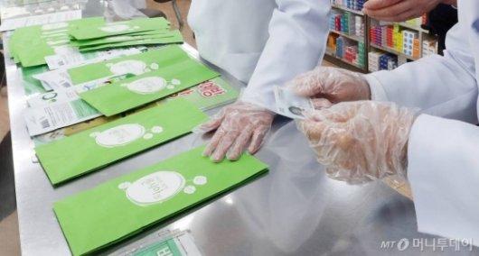한주에 1인 2장으로 제한되는 '마스크 5부제' 시행 첫 날인 9일 오후 서울 종로구의 한 약국에서 신분증 확인을 하고 있다. / 사진=김휘선 기자 hwijpg@