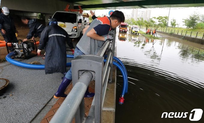 전국적으로 많은 비가 내리고 있는 13일 세종시 한국중부발전 세종본부 앞 도로가 침수돼 소방 및 지자체 관계자들이 긴급 복구작업을 하고 있다. 2020.7.13/뉴스1 © News1 장수영 기자