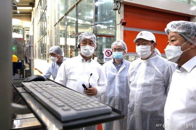 지난 3일 롯데 신동빈 회장(오른쪽에서 두 번째)이 경기 안성시에 위치한 롯데칠성음료 스마트팩토리를 찾아 코딩 검사기를 바라보고 있다. / 사진제공=롯데지주