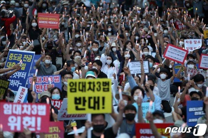 부동산 규제에 반발하는 시민들이 25일 저녁 서울 중구 예금보험공사 앞에서 '부동산 규제정책 반대, 조세저항 촛불집회'를 하고 있다./사진=뉴스1