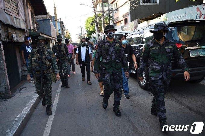 필리핀 경찰이 코로나19 감염자 폭증으로  봉쇄된  필리핀 시내를  순찰 하고 있다.© AFP=뉴스1