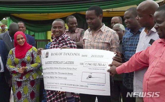 [메레라니(탄자니아)=AP/뉴시스]사니누 라이저(가운데 왼쪽)가 정부로부터 받은 77억4415만2703.82 탄자니아 실링(340만 달러) 수표를 들어보이고 있다. 2020.8.4