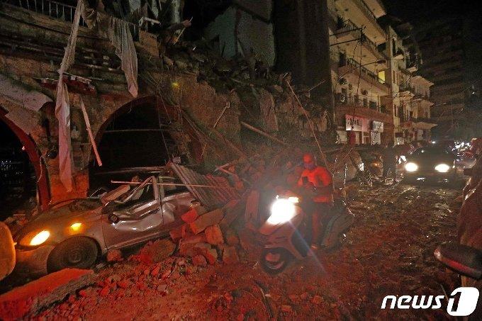 4일(현지시간) 레바논 수도 베이루트에서 일어난 대규모 폭발사고로 무너진 건물들. 잔해 앞으로 오토바이와 자동차가 지나가고 있다. © AFP=뉴스1