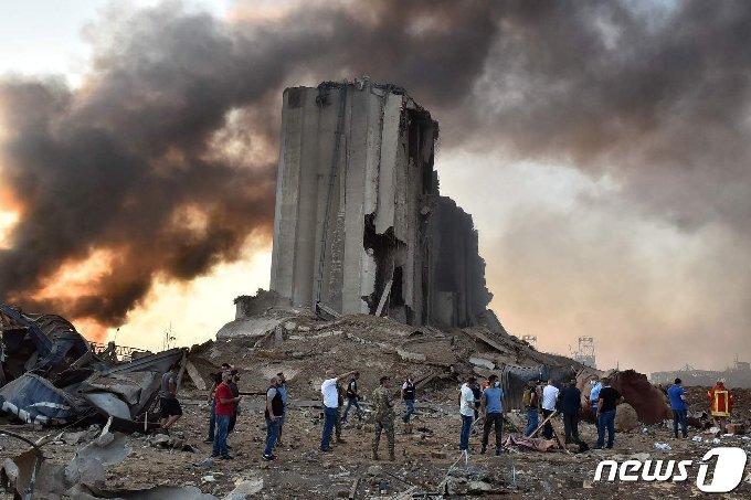 4일(현지시간) 레바논 수도 베이루트에서 일어난 대규모 폭발사고로 무너진 건물 앞에서 당국자들이 현장조사를 실시하고 있다. © AFP=뉴스1