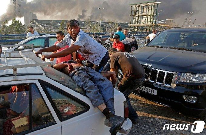 4일(현지시간) 레바논 베이루트항 선착장에 있는 창고에서 대규모 폭발사고로 부상을 당한 시민이 차량에 기대어 누워 있다. 이날 폭발로 최소 70여명이 숨지고 3,700명이 부상을 당해 수천명의 사상자가 발생했다. © AFP=뉴스1 © News1 우동명 기자