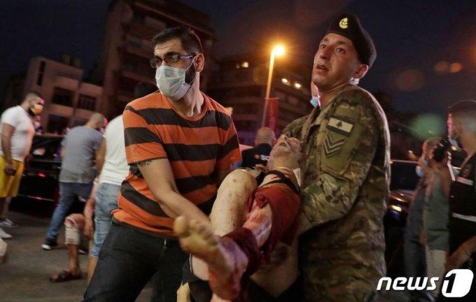 4일(현지시간) 레바논 베이루트항 선착장에 있는 창고에서 대규모 폭발사고로 부상을 당한 사람을 군인과 시민들이 병원으로 옮기고 있다. 이날 폭발로 최소 70여명이 숨지고 3,700명이 부상을 당해 수천명의 사상자가 발생했다./사진=(AFP=뉴스1)