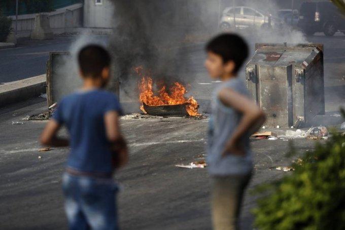 [베이루트=AP/뉴시스]6월 30일(현지시간) 레바논 베이루트에서 반정부 시위대가 도로를 봉쇄하기 위해 불을 지른 타이어와 쓰레기통 앞에 두 소년이 서 있다. 2020.07.01.