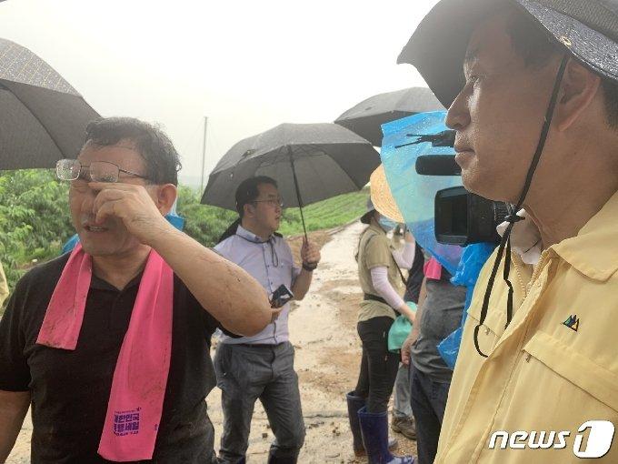 5일 주호영 통합당 대표가 충주시 엄정면 비석마을 산사태 피해 현장에서 조길형 충주시장(오른쪽)과 이야기를 나누다가 눈에 들어간 빗물을 닦아내고 있다.2020.8.5/© 뉴스1