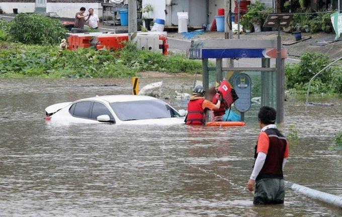 6일 경기 파주시 파평면 율곡리 일대 도로가 폭우로 인한 임진강 수위 상승으로 물에 잠긴 가운데 주행 중이던 차량이 침수되어 119 구조대원이 운전자를 구조하고 있다. / 사진=뉴시스