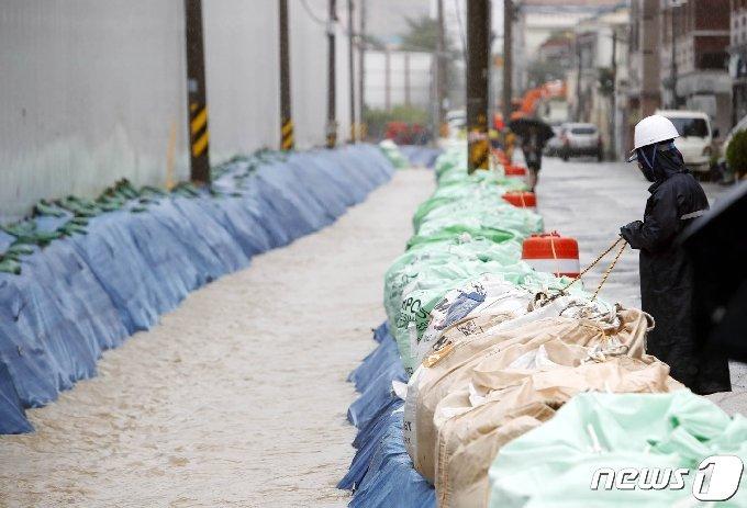 호우 경보가 내린 8일 오후 광주 북구 한 도로에서 구청 직원들이 모래주머니를 쌓는 복구작업을 진행하고 있다.(광주북구 제공) 2020.8.8/뉴스1 © News1