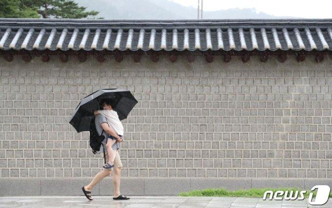 서울 전역에 호우경보가 발효된 2일 서울 종로구 세종대로 인근에서 한 시민이 우산을 쓴채 아이를 안고 발걸음을 재촉하고 있다./사진=뉴스1