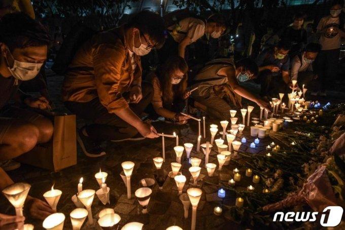 (홍콩 AFP=뉴스1) 지난 6월 (현지시간) 홍콩 시민들이 텐안먼 시위 31주년을 맞아 침사추이 해변에서 시위 희생자를 추모하는 촛불을 켜고 있다.   ⓒ AFP=뉴스1