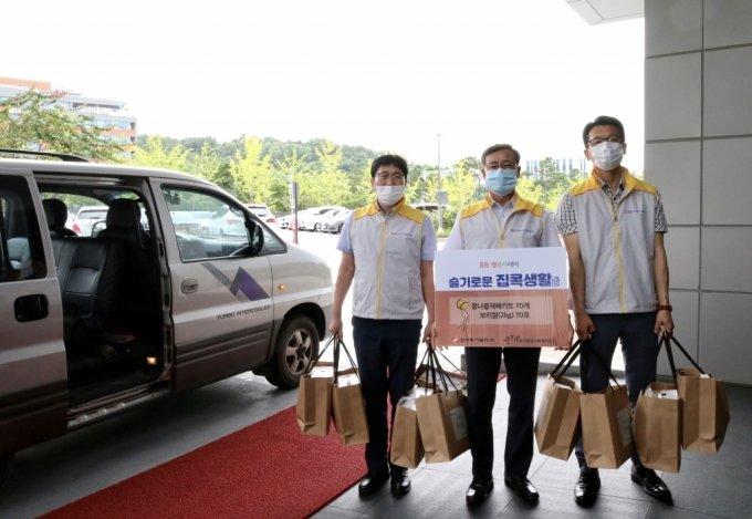 권혁만 한국동서발전 기전기술실장(가운데)과 직원들이 기부 물품을 전달할 차량 앞에서 기념 촬영을 하고 있다.    /사진제공=한국동서발전