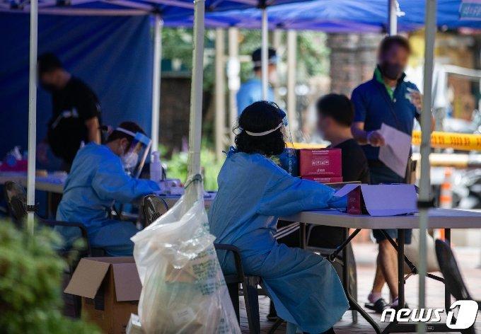 14일 서울 중구 통일상가 인근에 마련된 신종 코로나바이러스 감염증(코로나19) 임시 선별진료소에서 시민들이 검체검사를 받기 위해 대기하고 있다./뉴스1 © News1